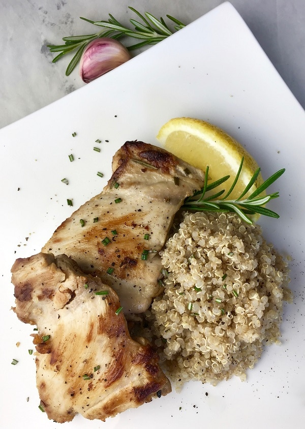 rosemary lemon chicken thighs with quinoa and a lemon wedge on a white plate