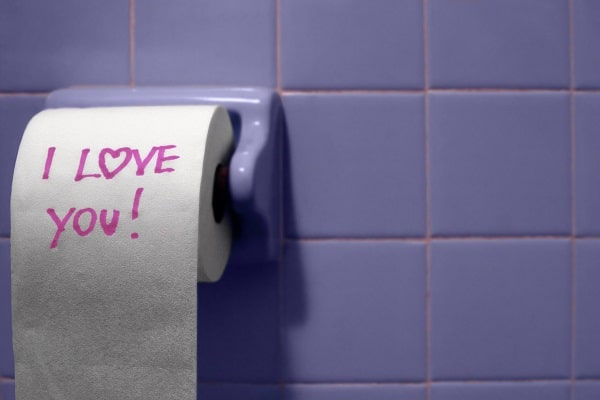 a toilet paper roll on a blue tiled wall with the words I Love You written on the toiled paper with pink marker