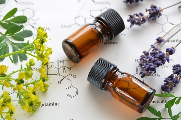 two bottles for essential oils and yellow and purple flowers on top of a paper with different molecules drawn on it