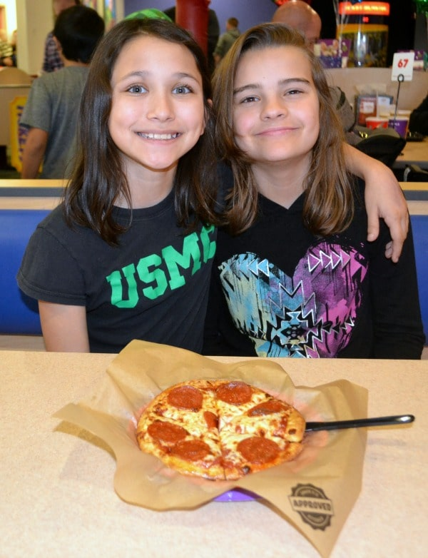 two girls smiling with a pepperoni pizza on the table in front of them at the chuck e cheese