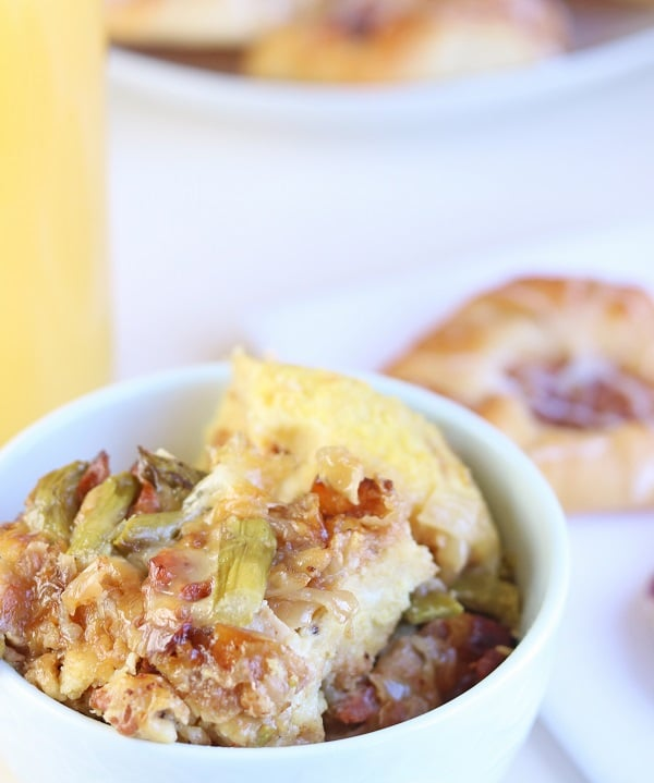 close up view of bacon and asparagus strata in a white bowl with a danish in the background