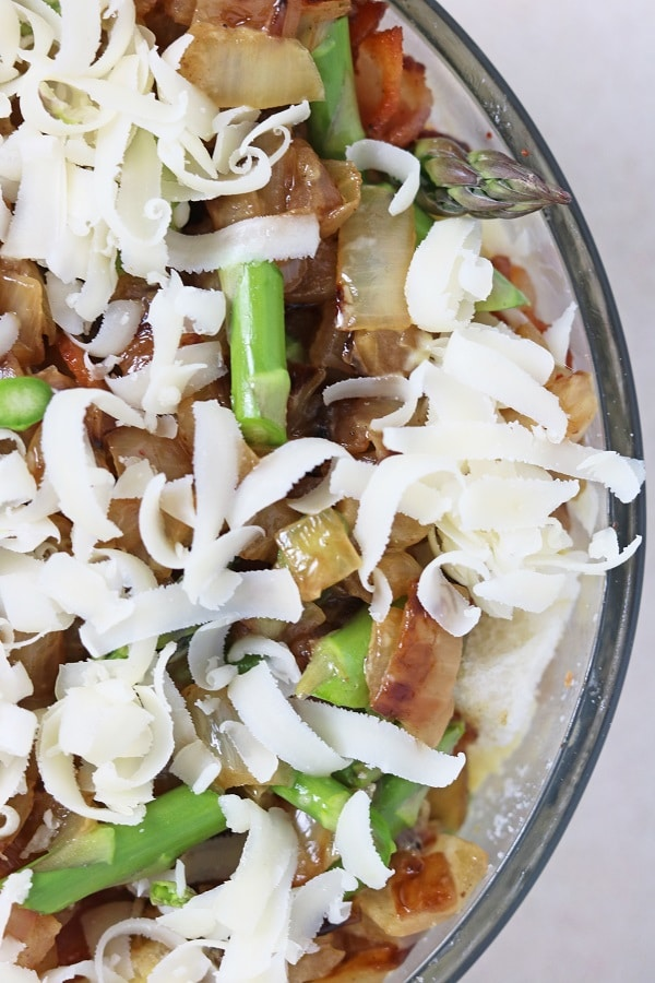a glass bowl of egg mixture, bacon, onions and asparagus topped with shredded swiss cheese