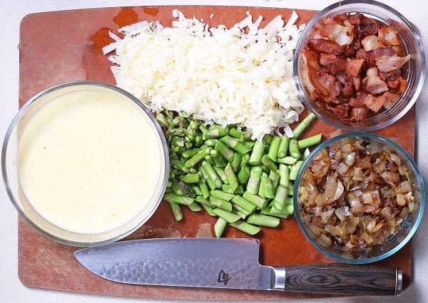 egg mixture, bacon, cooked onions in glass bowls, shredded cheese, chopped asparagus and a knife on a wood cutting board