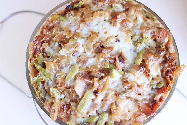 overhead view of overhead view of bacon and asparagus strata in a glass bowl on a white background