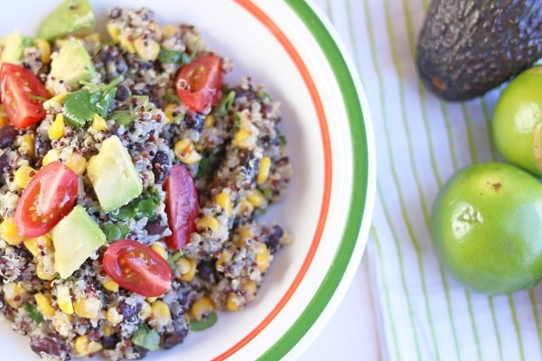 quinoa black bean salad in a white, orange and green bowl next to limes and avocado on a cloth