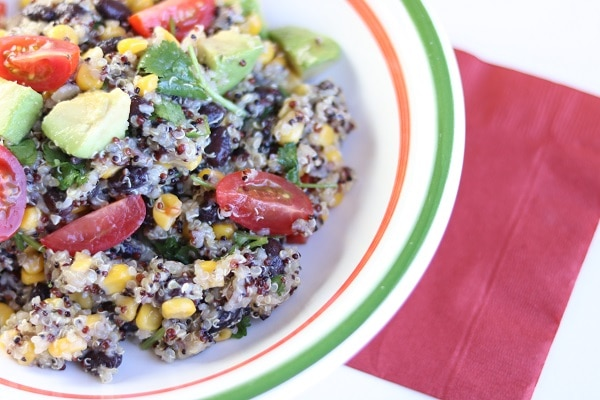 quinoa black bean salad in a white, orange and green bowl on a red napkin on a white table