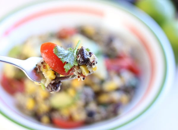 a fork full of quinoa black bean salad above a white, orange and green bowl of more salad