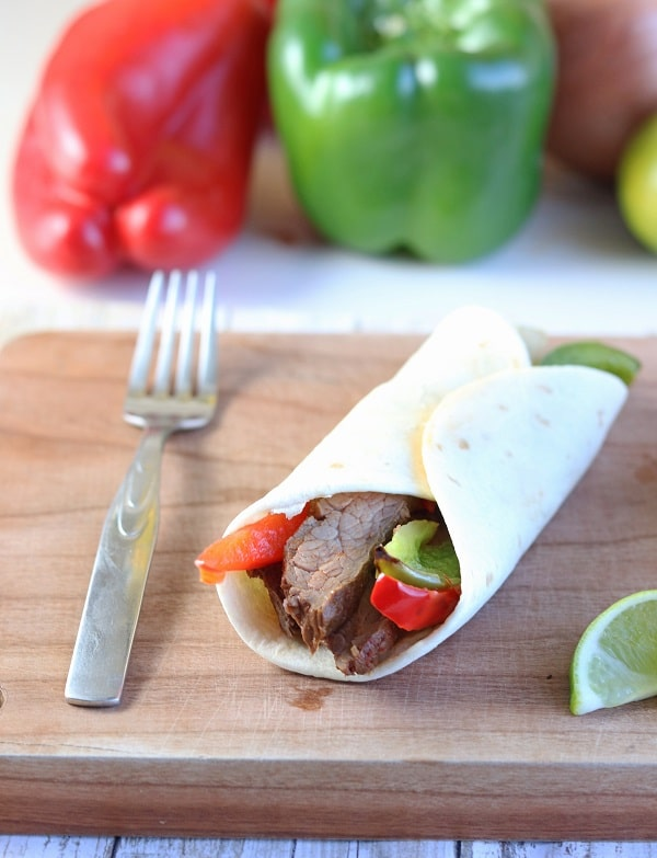 a steak fajita next to a fork and a lime wedge on a wood cutting board with a red and green pepper in the background