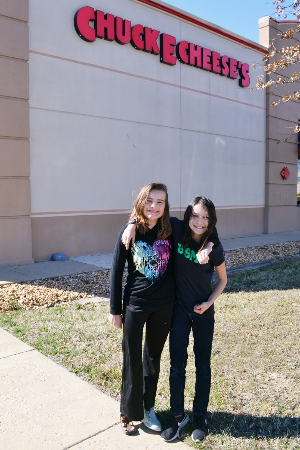 two girls standing in front of a chuck e cheese's building