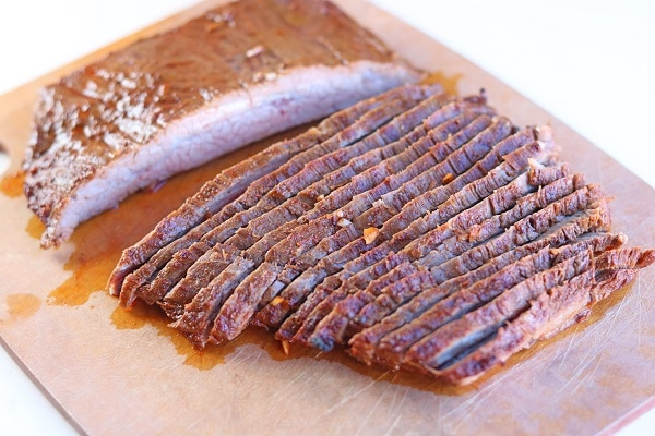 sliced steak on a wood cutting board on a white background