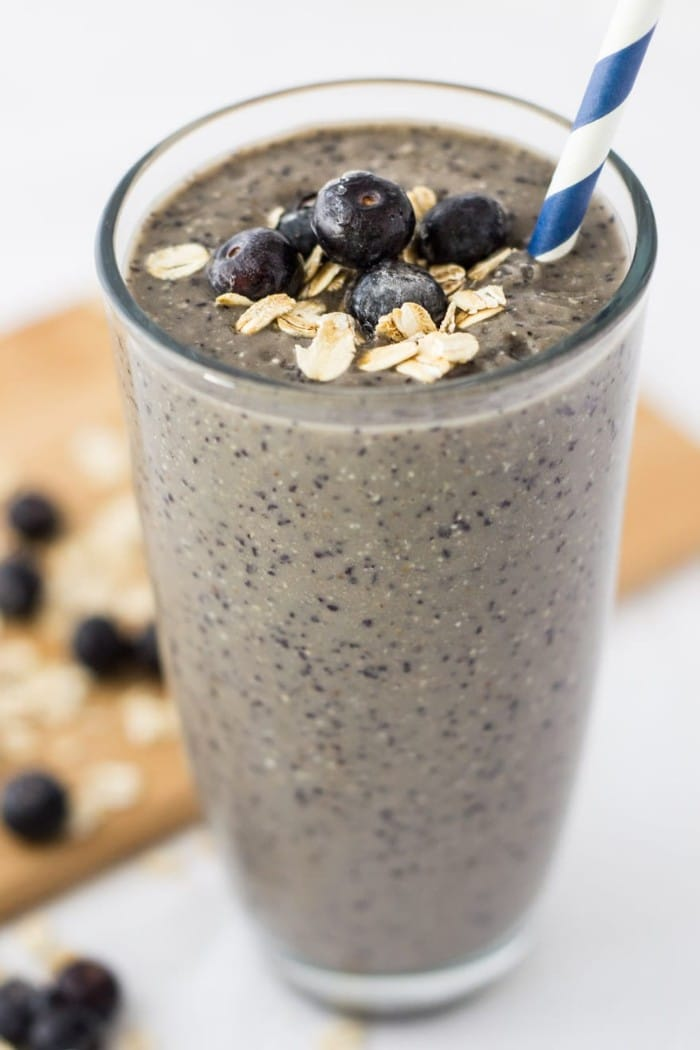 blueberry banana oatmeal smoothie topped with blueberries and oats in a glass with a blue and white straw in it on a white table with more blueberries and oats on a wooden cutting board in the background