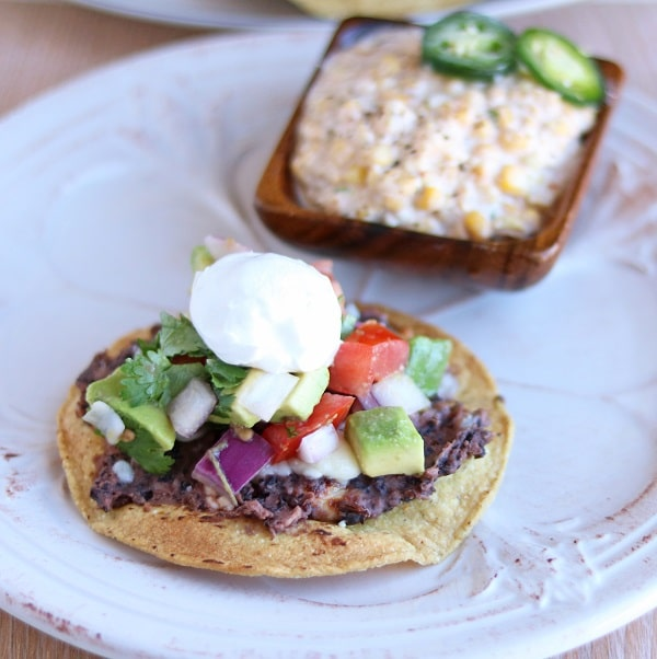 black bean tostada and mexican corn salad on a white plate