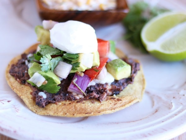 a black bean tostada topped with sour cream on a white plate with half a lime and a brown bowl of mexican corn salad in the background