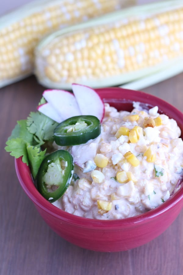 creamy mexican corn salad topped with sliced jalapenos in a red bowl on a brown table with two corn on the cob in the background