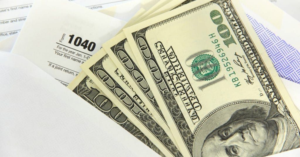 some hundred dollar bills on top of a 1040 tax refund form and some envelopes