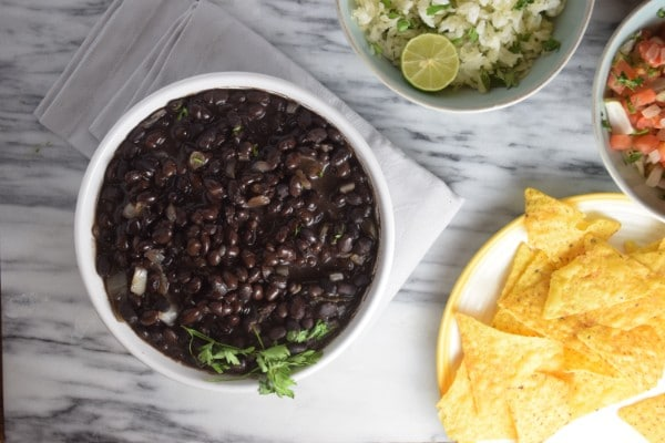 overhead view of black beans in a white bowl on a white cloth with bowls of rice, salsa and chips in the background