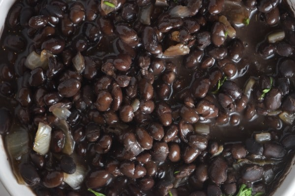 overhead view of black beans in a white bowl