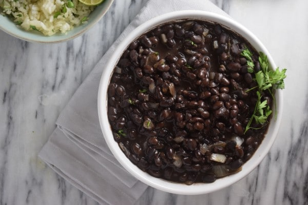 overhead view of black beans in a white bowl on a white cloth with a bowl of rice in the background