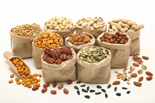 paper bags filled with different kinds of nuts on a white table with more nuts and a scoop on the table
