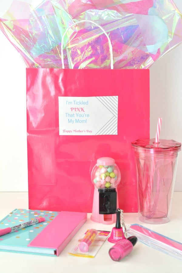 a pink bag with cellophane in it with a label on it reading, I'm tickled pink that you're my mom Happy Mothers Day, with a pink mini gumball machine, pink cup, pink notebook and pen, pink lip gloss, nail polish and an emery board in front of the bag, all on a white background