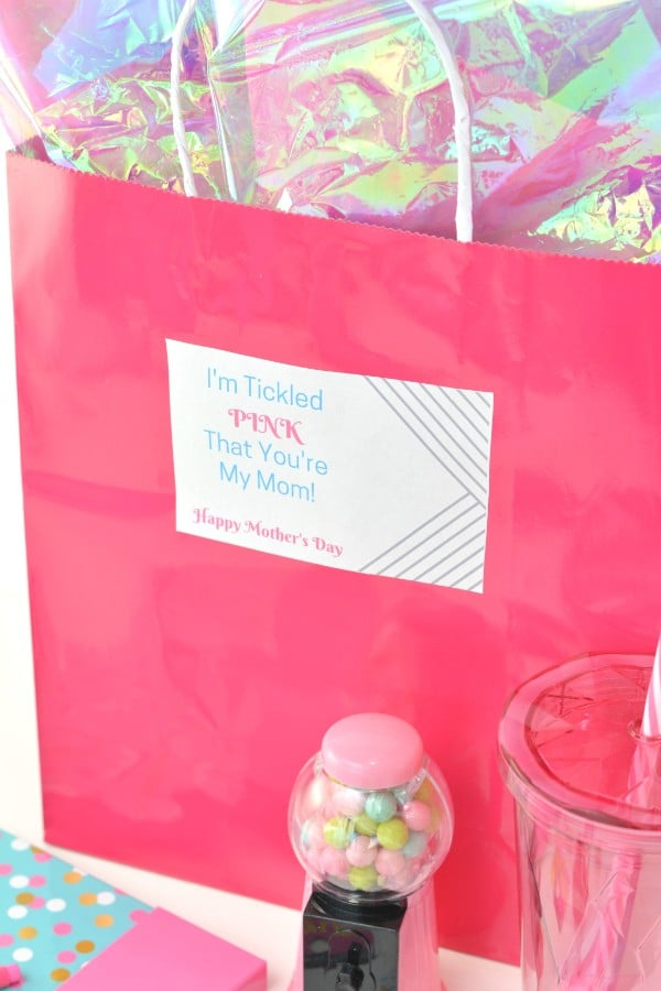 a pink bag with cellophane in it with a label on it reading, I'm tickled pink that you're my mom Happy Mothers Day, with a pink mini gumball machine, pink cup, pink notebook in front of the bag, all on a white background
