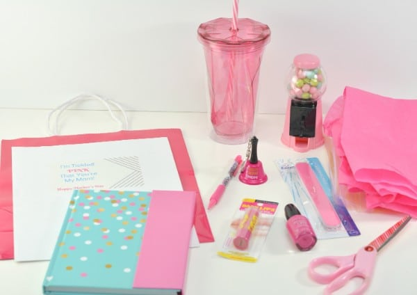 a pink bag with a paper on it reading, I'm tickled pink that you're my mom Happy Mothers Day, with a pink mini gumball machine, pink cup, pink notebook and pen, pink lip gloss, nail polish and an emery board, scissors and tissue paper next to it, all on a white background
