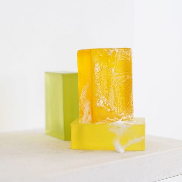two yellow bar soaps, and a green bar soap on a white background
