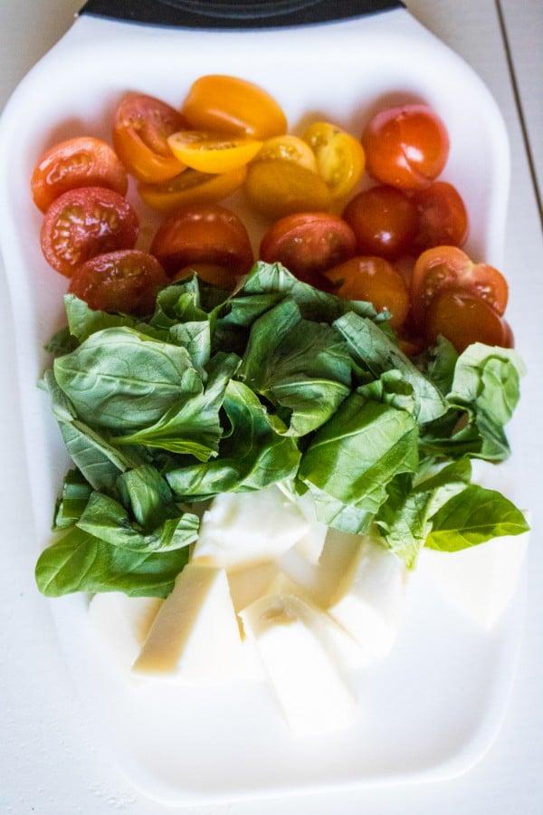 sliced grape tomatoes, fresh basil, mozzarella on a white plate