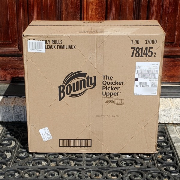 a cardboard box of bounty outside on a door mat with a brown door in the background