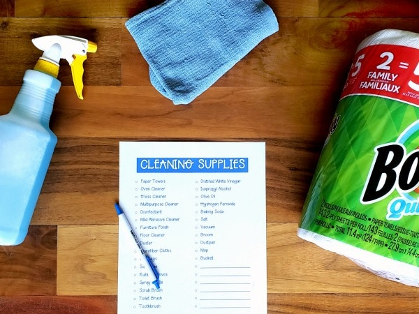 a spray bottle with blue liquid in it, a blue cloth, printable cleaning supplies list with a pen on it, bounty paper towels, all on a brown table