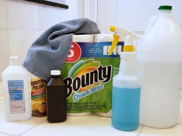 rubbing alcohol, furniture polish, hydrogen peroxide, blue liquid in a spray bottle clear liquid in a jug, bounty paper towels, and a blue cloth on a white bathroom counter