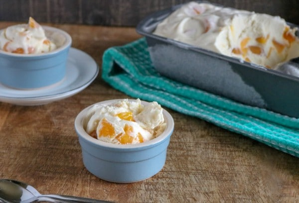 peach ice cream in two blue bowls, one of them on a white plate next to a metal pan of ice cream on a green linen, all on a brown table