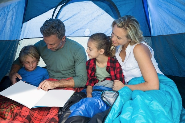 a mom, dad, boy and girl in a tent with blankets on their legs, reading a book together
