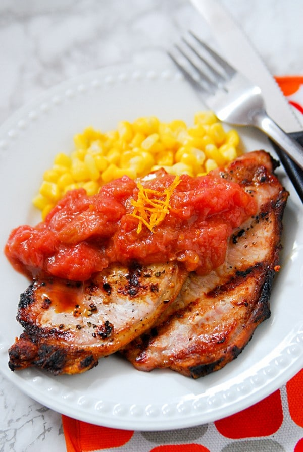 pork chops topped with rhubarb orange sauce and corn on a white plate next to a fork