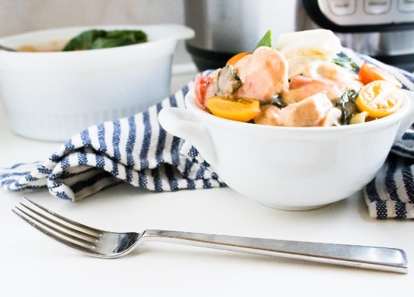 caprese chicken in a white bowl on a blue and white striped linen with an instant pot and another bowl of chicken in the background