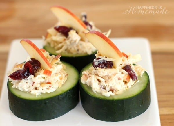 cranberry apple chicken salad in cucumber cups on a white cutting board on a brown table