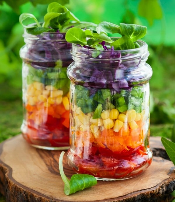 rainbow salad in two glass jars on a log