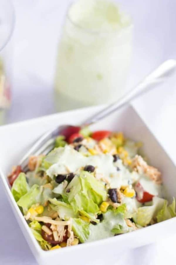 chopped Mexican salad in a white bowl with a fork in it with a jar of dressing in the background