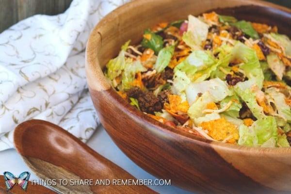 Doritos taco salad in a wooden bowl next to a wooden spoon on a white table next to a white and gold linen
