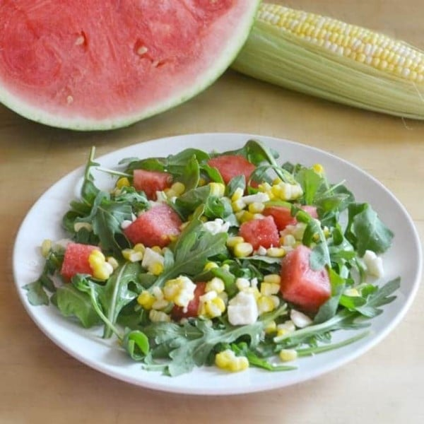 sweet corn and watermelon salad on a white plate on a wood table with a watermelon and corn on the cob in the background