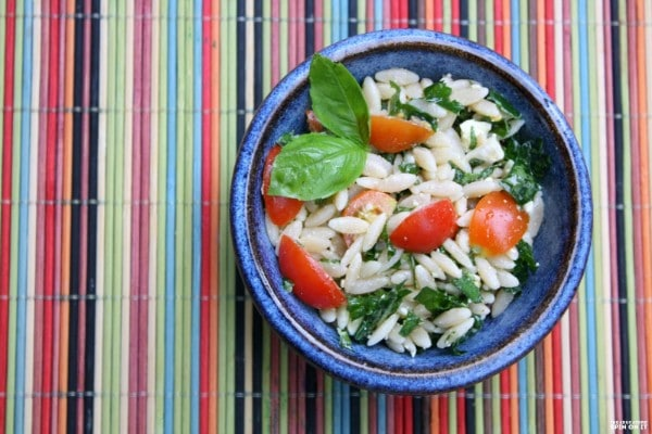 kale, orzo and feta salad in a blue bowl on a multi-colored mat