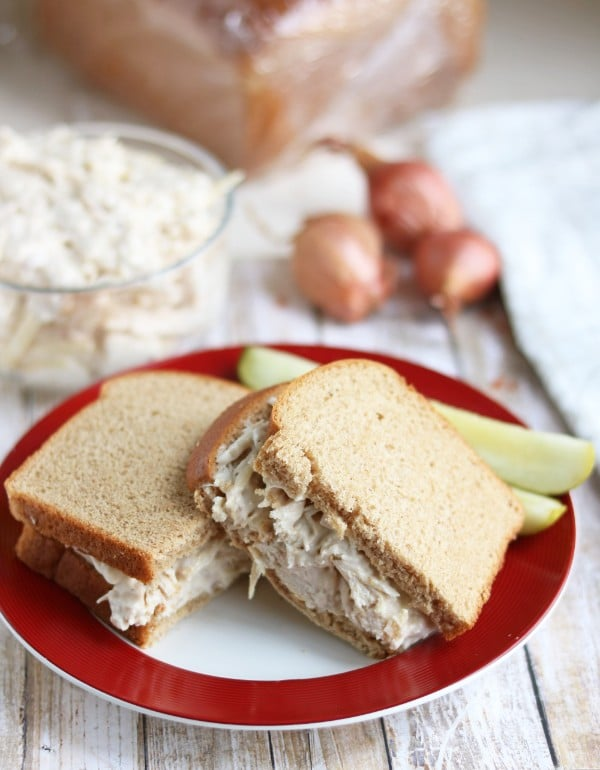 a caesar chicken salad sandwich on a red and white plate with two pickles on it on a wood table with a glass bowl of more chicken salad in it and shallots in the background