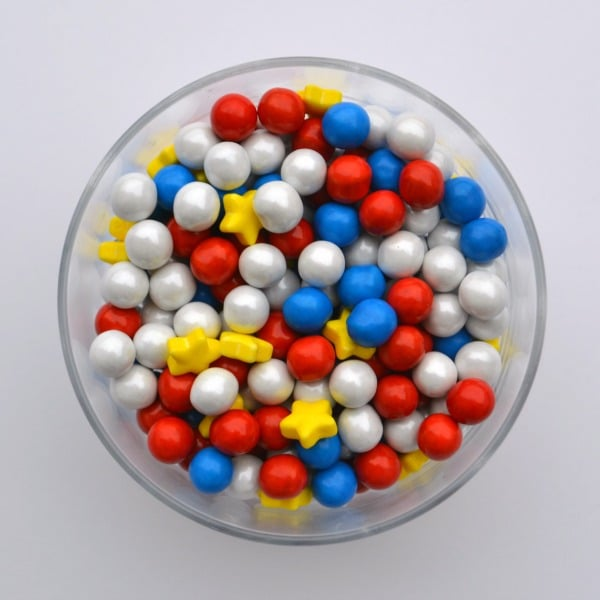 an overhead view of a glass bowl of red, white and blue round candies and yellow stars on a white table