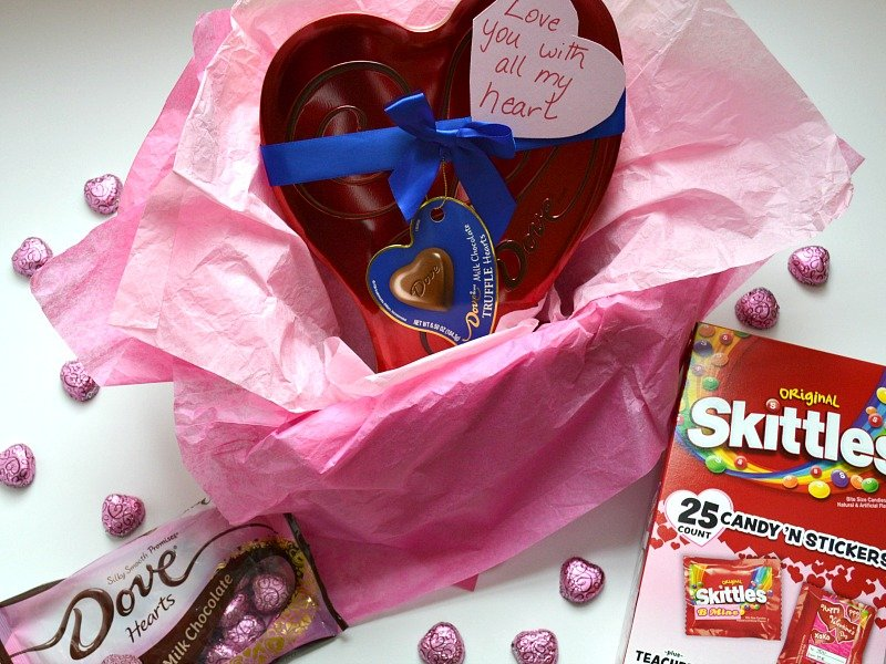 valentines skilttles, dove hearts on a white table next to a box filled with pink tissue paper and a dove heart candy box with a note reading love you with all my heart