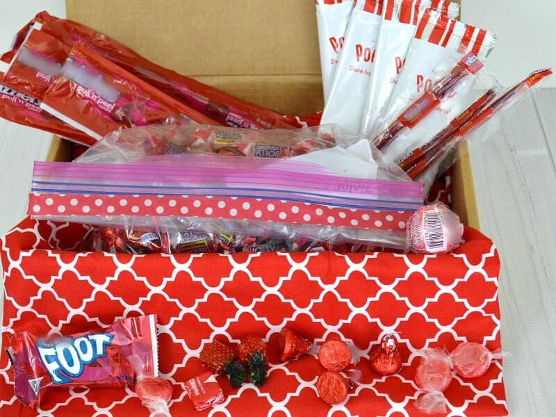 a red cardboard box full of various candy, like kisses, pockies, and twizzlers on a white table