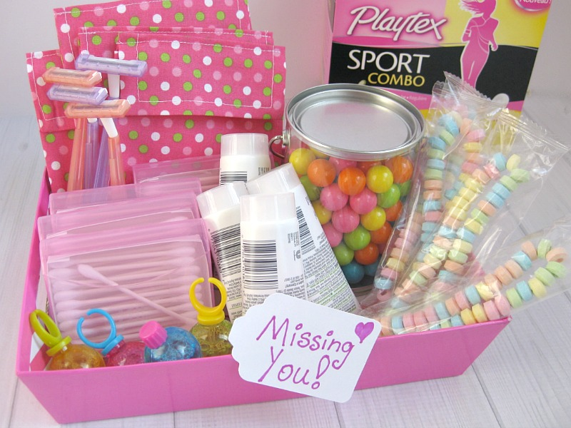 a pink box with a paper tag that reads missing you with qtips, lotion, candy, cloth bags, razors and playtex in it on a white wood table