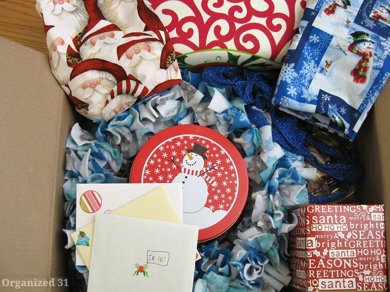 card envelopes, a snowman tin, blue and red christmas decorations and a couple of wrapped presents in a cardboard box