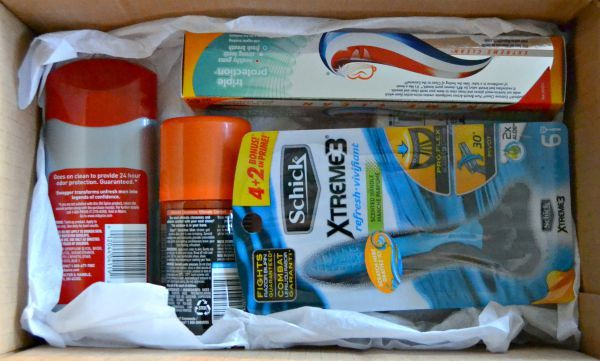 deodorant, shaving cream, razors and toothpaste in a cardboard box with tissue paper in it