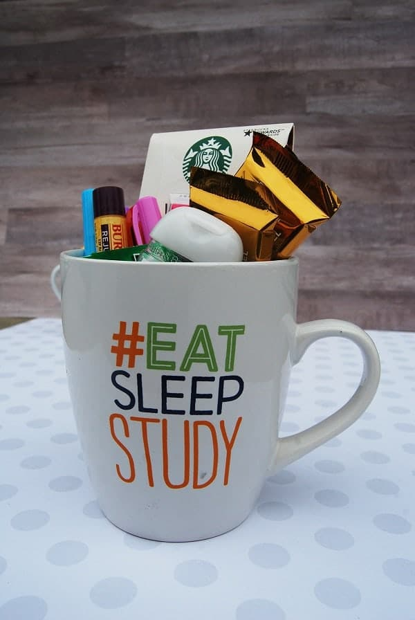 various candy, gum, chapstick, pink pen, starbucks gift card in a white mug with text #eat sleep study on a white polka dot paper with a brown background