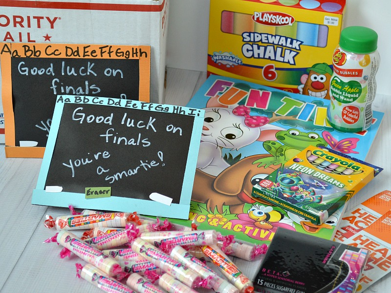 a priority mail cardboard box, sidewalk chalk, bubbles, coloring book, crayons, gum, smarties candies, and two paper chalkboards with text reading Good luck on finals you're a smartie! on a white background